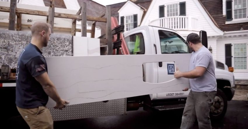 Two Paul White Company team members unloading a custom cut stone from the Portland Maine stone shop before a residential installation