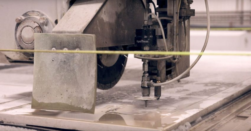 Photo of a machine in the Paul White Company stone shop in Portland Maine custom cutting a stone slab